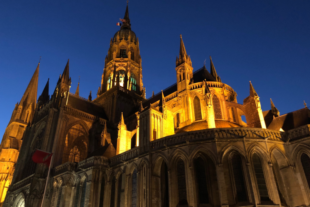 The cathedral in Bayeux France lit up against the darkening sky. There is so much to do and some great places to stay in Bayeux France.