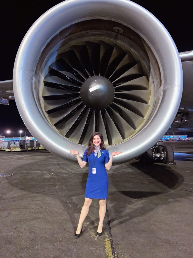 flight attendant in front of plane engine