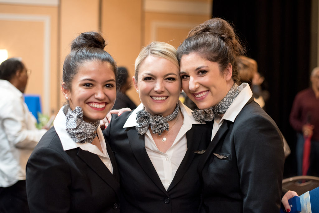 a group of three young women. They are smiling. Their hair is pulled up into buns on their head and they are dressed in navy blue flight attendant jackets with scarves on their necks.