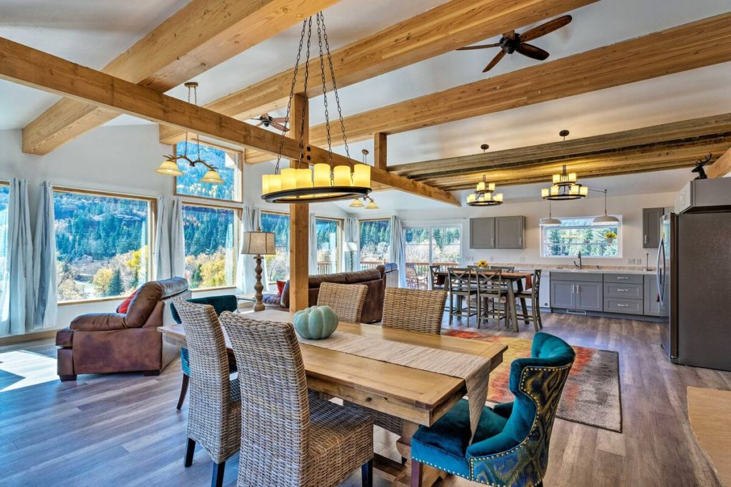 View of dining area and kitchen of one of the Ouray Colorado cabins to rent. The ceiling is vaulted and there are beams and a wooden floor. Huge picture windows surround the room with views to the San Juan mountains.