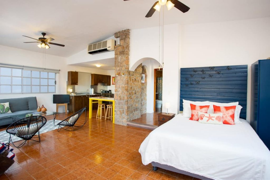 The interior of a studio airbnb in Cabo. There is a bed with a white coverlet. A little sitting area and you can see a kitchen in the back of the room.