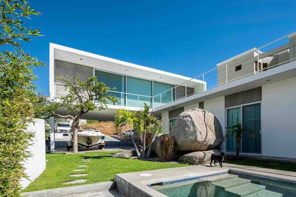 Exterior of A very modern looking home in white and grey. There is a small pool in the foreground. This is one of the Airbnbs in Cabo San Lucas.