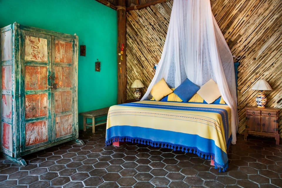 El Nido Airbnb in Cabo San Lucas. The photo is of a bed with a brightly covered yellow and blue blanket. The floors are tile and the wall is painted a bright green. There is a mosquito netting over the bed.