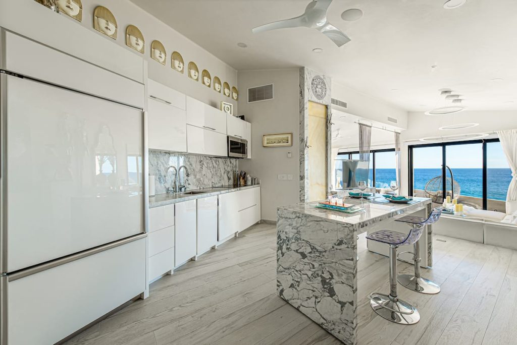 The kitchen of a sleek and modern condo. The cabinets are a bright and shiny white and the granite is grey and white. The floors are a light wood.
