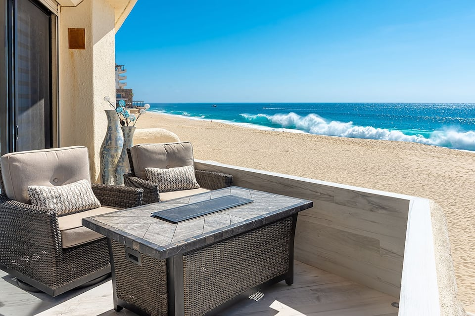 the private patio of a condo. The beach is immediately outside and the water is very blue and the wave are crashing on the sand.