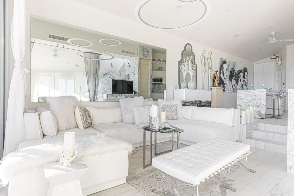 The interior of a sleek and modern condo. Everything in the condo is white including the furniture, walls, and flooring. It looks very plush.