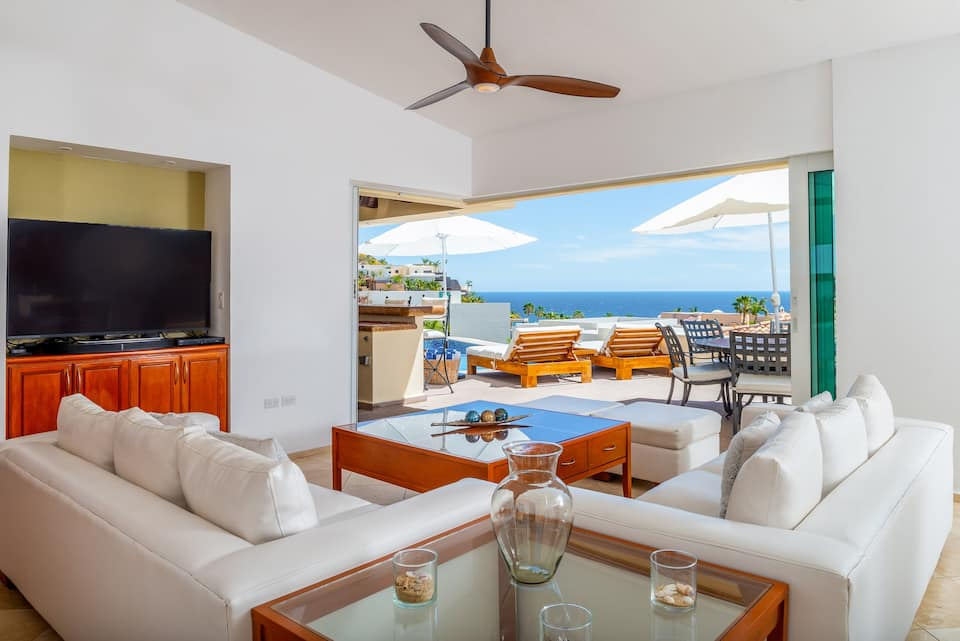 A lovely living area with white walls and white sofas with glass and wood furniture. It looks out onto a pool and deck. You can see the ocean in the background.