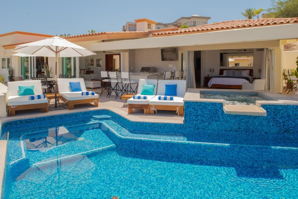 View of a beautiful pool with deck chairs and umbrellas looking into a house.