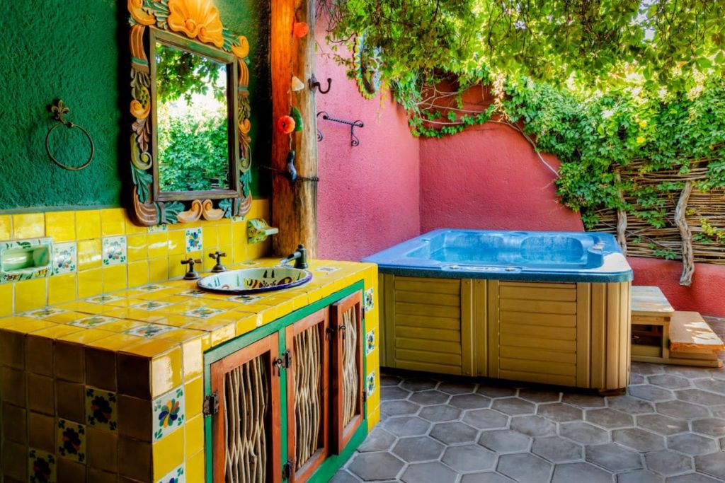 The open air area of an airbnb in cabo san lucas. There is a cabinet with a sink. The cabinet is covered in bright yellow tile and the wall is painted green. There is a mirror above the sink. In the background there is a hot tub. Vines are growing above the tub and there is a dark pink wall on two sides of it with the rest open to the air.