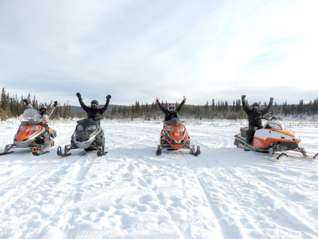 Four people on four snowmobiles on a frozen snowy lake outside of Fairbanks, Alaska.
