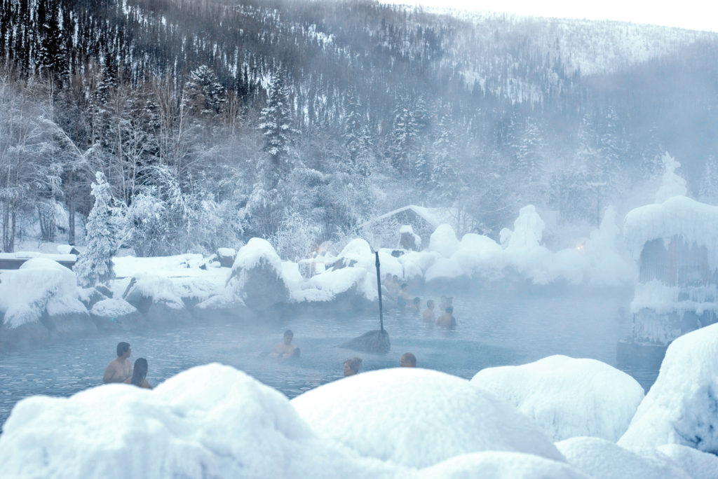 Steam rising into the air from Chena Hot Springs just outside of Fairbanks, Alaska. People are in the spring and snow is everywhere around it.