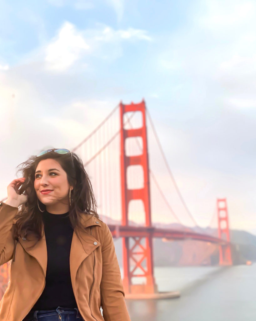 Young woman sitting in front of the Golden Gate Bridge. She has dark hair, her glasses are on her head. She is wearing a black shirt with a brown suede jacket and blue jeans.