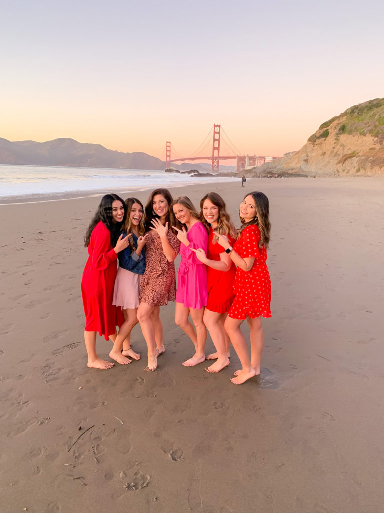 6 girls on Baker Beach in San Francisco. They are all dressed in shades of pink and red. The bridge is in the background. One girl is showing her hand in as if she has just gotten engaged.