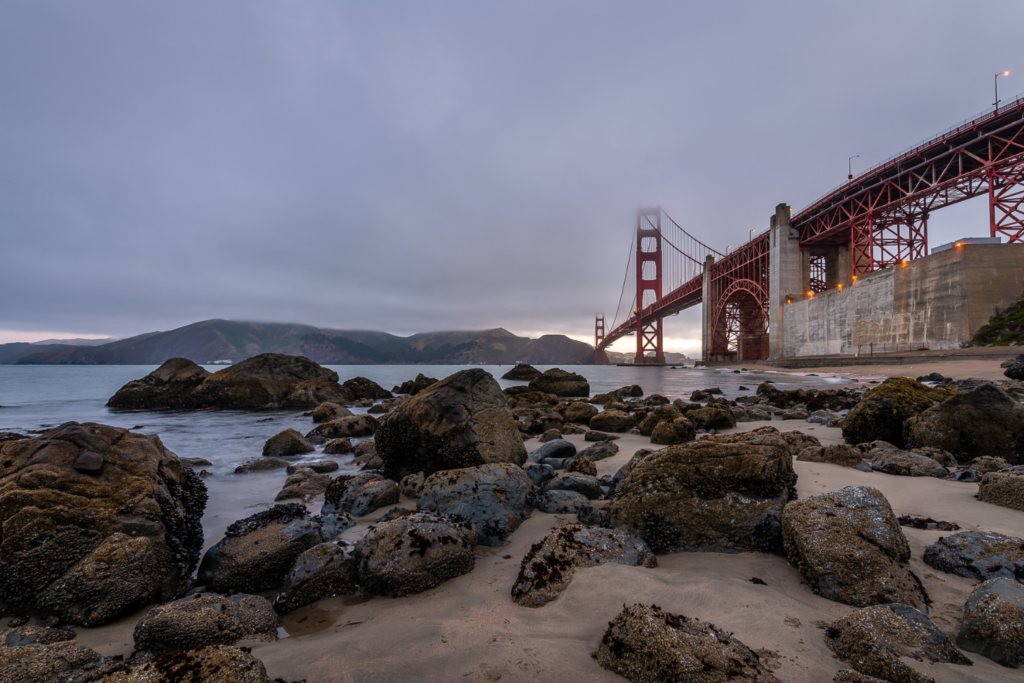 Golden Gate Bridge at dusk from Marshall's Beach. There are a bunch of rocks in the foreground in the water and on the beach. The bridge is in the background and the very top is shrouded in fog.