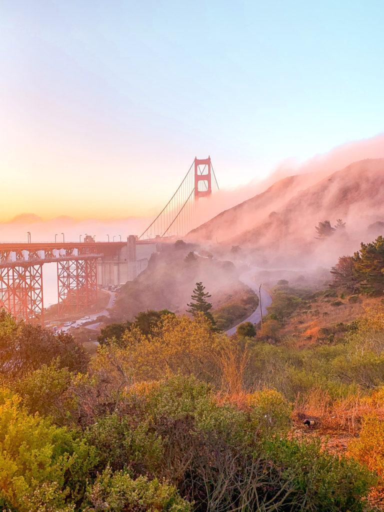 The golden gate bridge with fog around it.