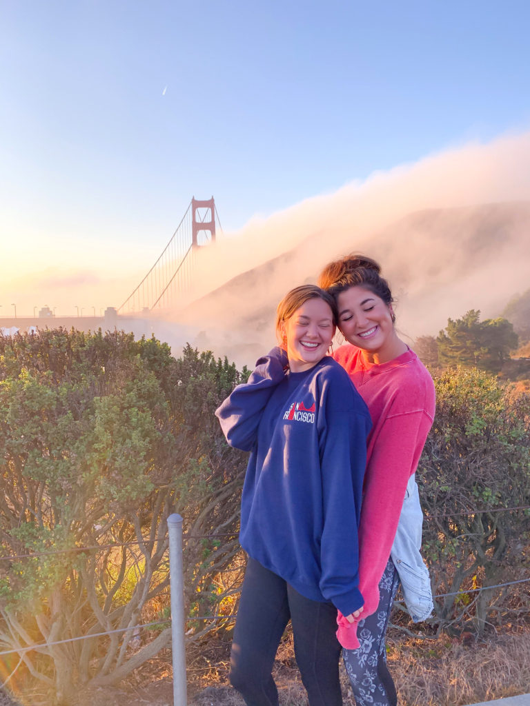 two girls at sunrise. They are standing together and their eyes are closed. You can barely see the golden gate bridge behind them because it is surrounded by fog.