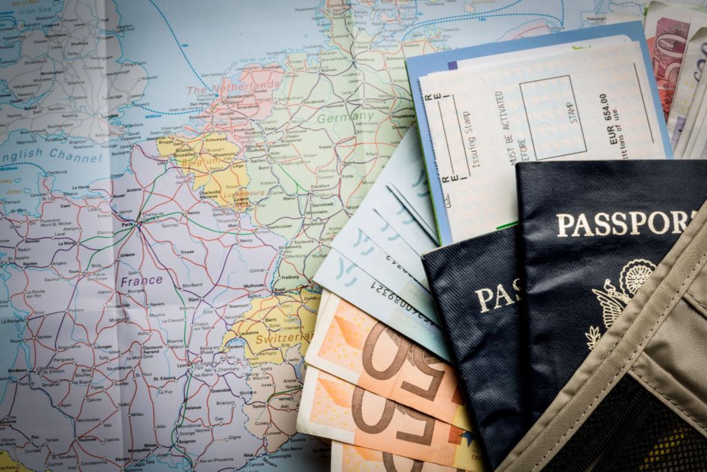 a passport and an airline ticket and some Euros on a map