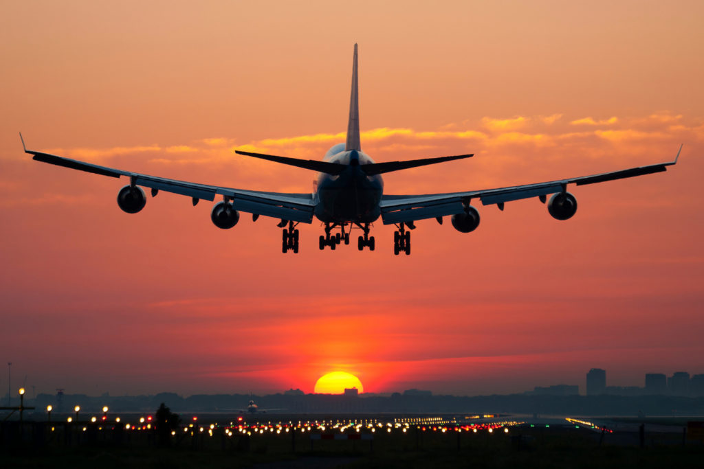 an airplane landing into the sunset. How to avoid getting airsick.
