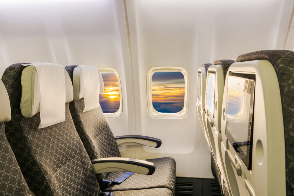 interior of an airplane. You can see a row of seats and there is a sunset outside of the airplane window. One tip for how to prevent airsickness is to look at the horizon