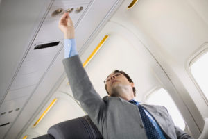 a man on an airplane turning on the air vent. A tip for how to avoid airsickness is to use the air vent