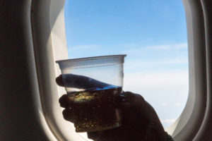 a hand holding a drink in front of an airplane window