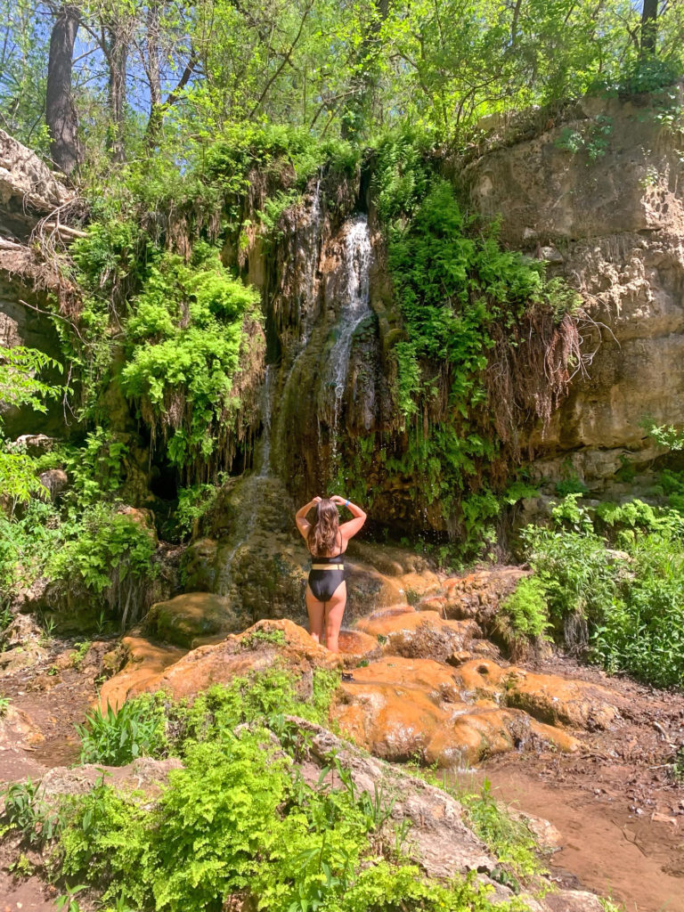 Girl in bathing suit at Krause Springs. In a 1 piece place bathing suit with a belt. Ideas for what to wear in Texas and what to pack for a trip to Texas.
