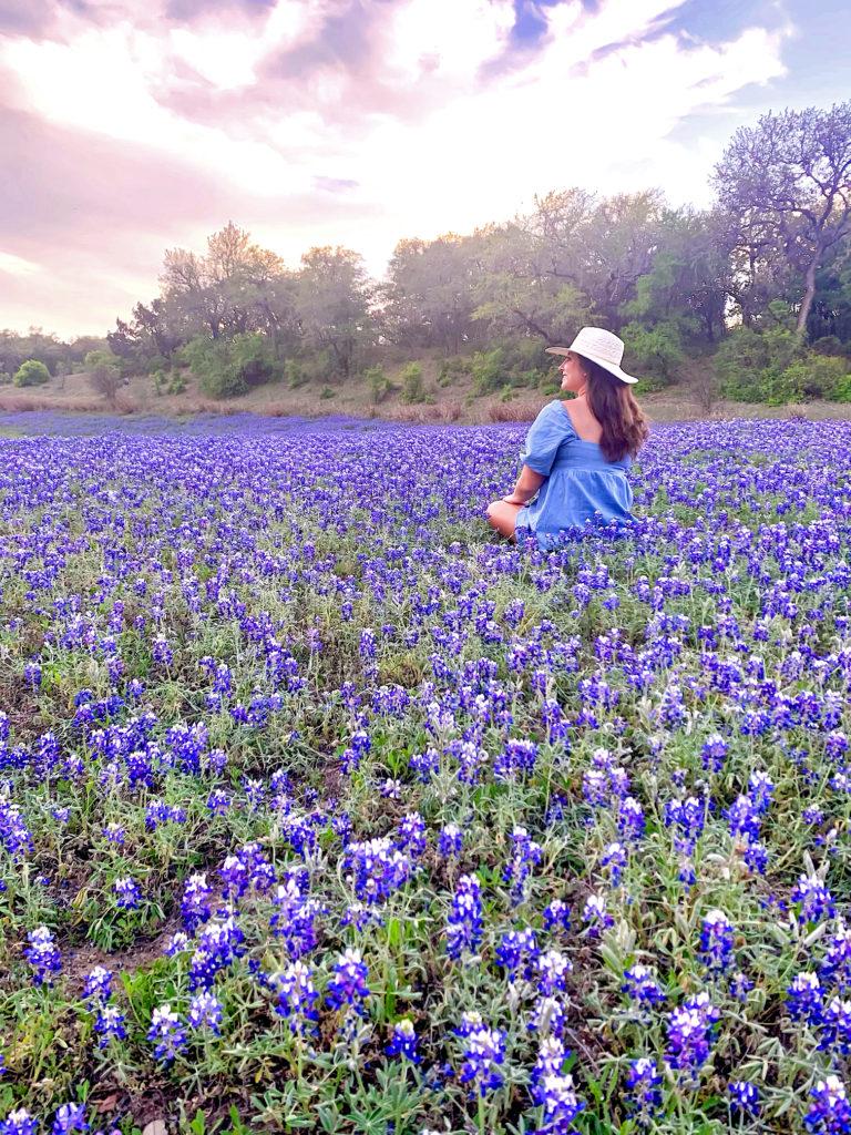 girl in a denim dress sitting in a field of flowers.