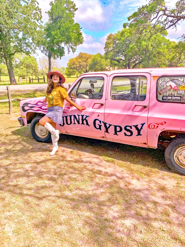 standing in front of the junk gypsy vehicle wearing white cowboy boots, a ginham skirt, and a graphic tee and a pink cowboy hat.