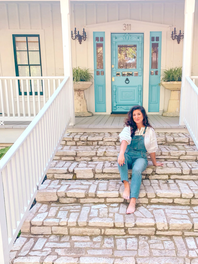 overalls with a white shirt with poofy sleeves. What to pack for a Texas Vacation.