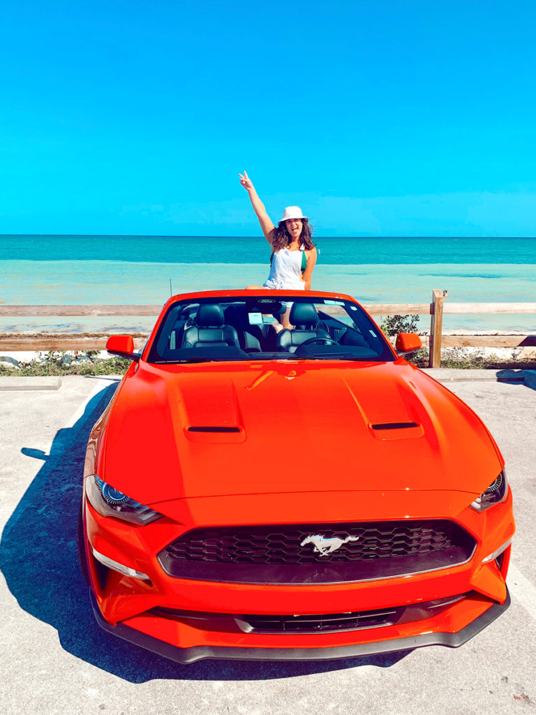 What to pack for the Florida Keys? A sun hat! Girl in a red convertible on the beach in the Florida Keys